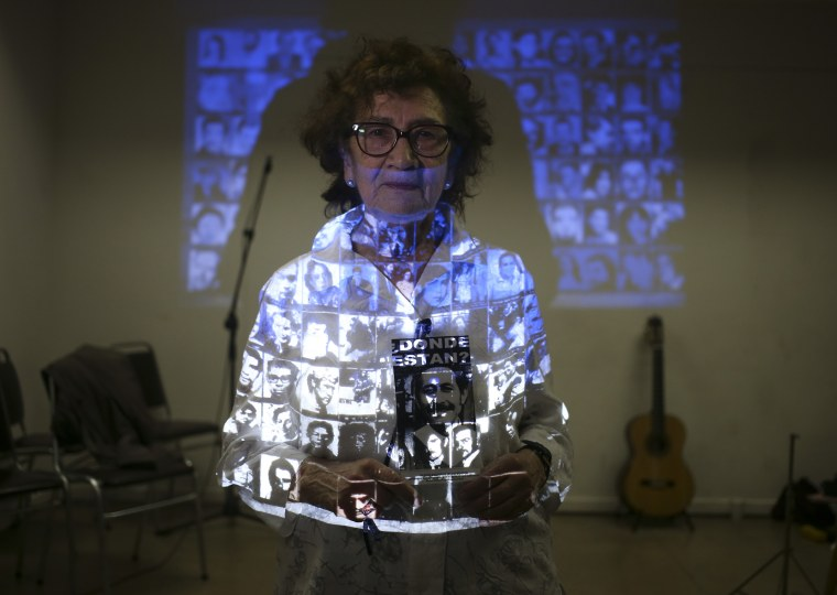 Violeta Zuniga poses for a portrait covered in projected photographs of people who were detained and disappeared during Chile's dictatorship