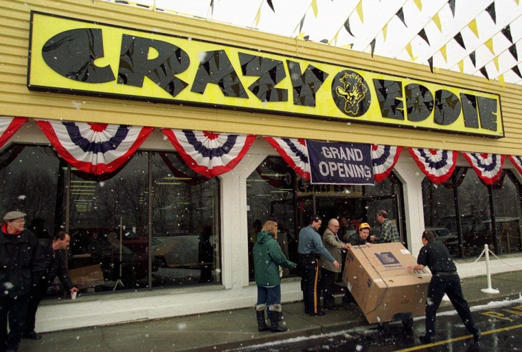 Image: Workers bring out a large-screen television at the grand opening of a new Crazy Eddie electronics store