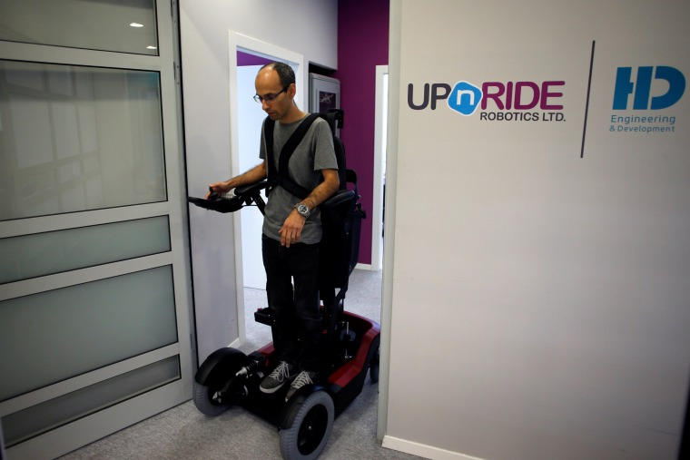 Image: An employee stands on a wheelchair developed by Israeli company UPnRIDE Robotics, that enables paralysed people with limited function in their arms to stand upright, during a demonstration at their offices in Yoqneam