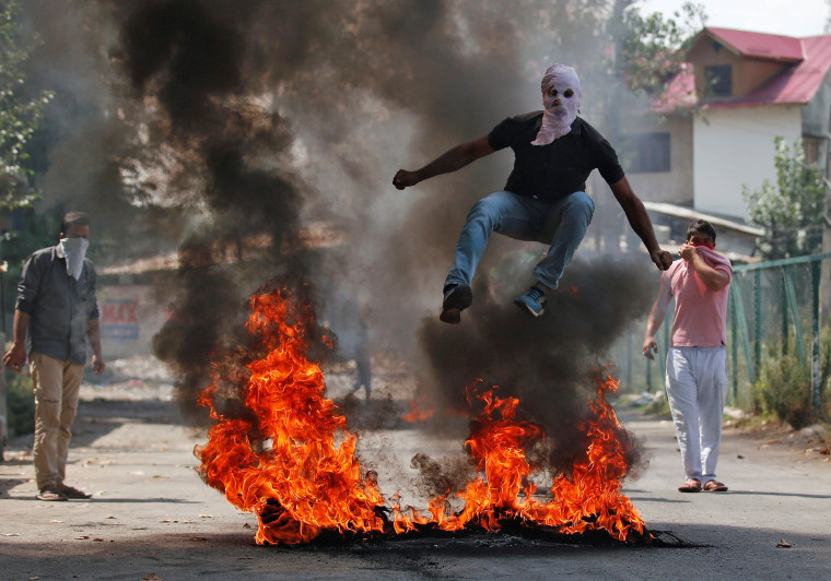 Image: A man in a balaclava jumps over burning debris during a protest against the recent killings in Kashmir, in Srinagar