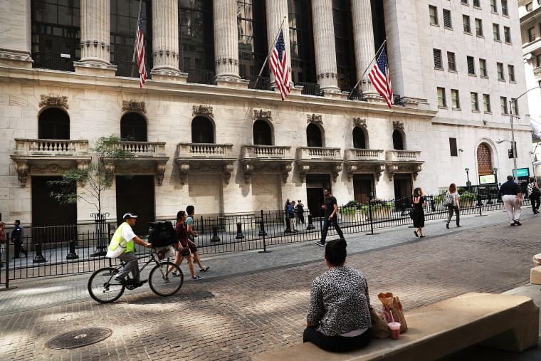 Image: People walk outside of the New York Stock Exchange