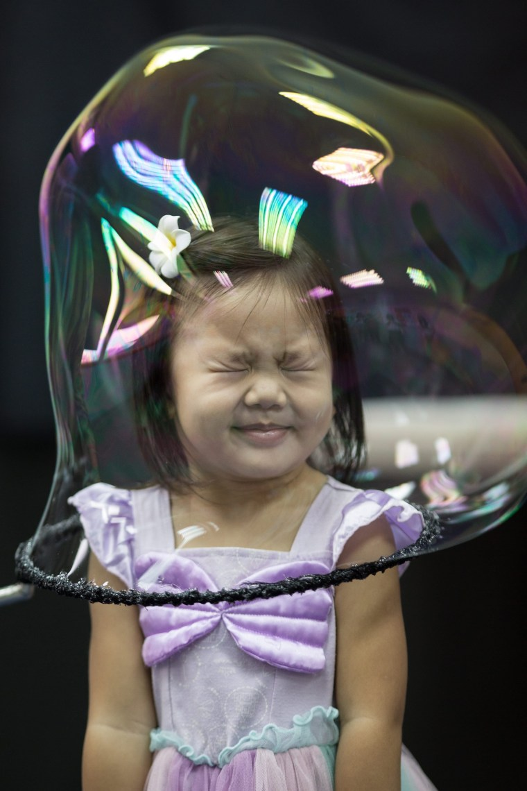 Image: A girl reacts as she stands in a soap bubble