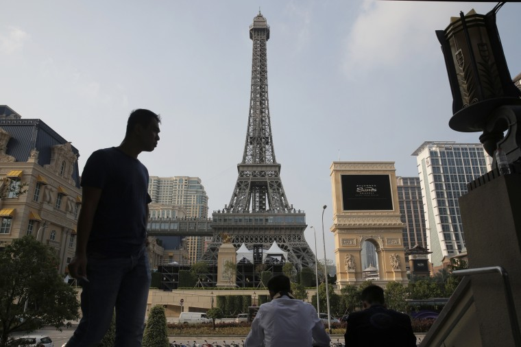 Image: People rest in front of a replica of the Eiffel Tower of Parisian Macao