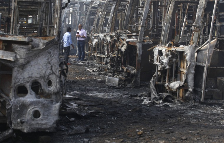 Image: A television journalist reports amidst the charred remains of passenger buses