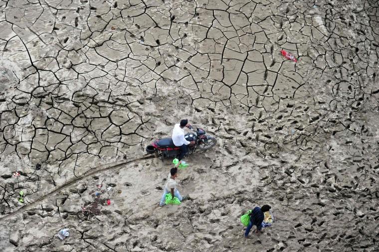Image: People cross a marshland area on the bank of river Yaumna