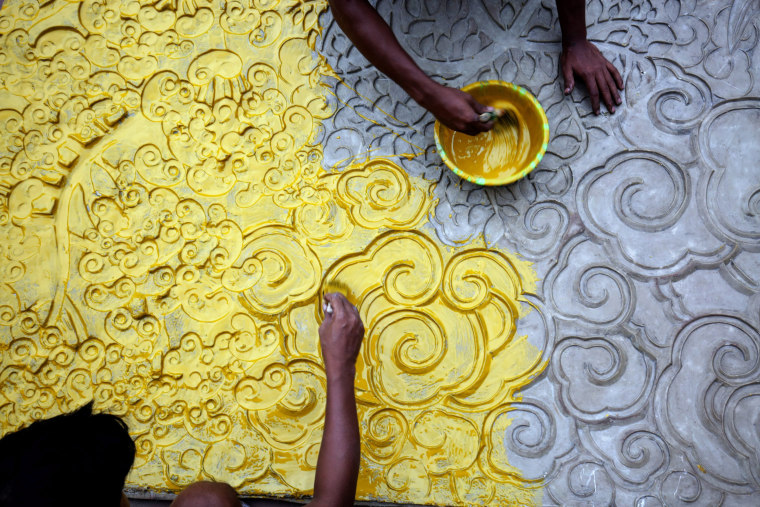 Image: Indian artists work on an art installation at a makeshift pandal