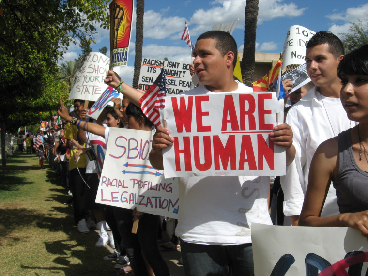 """Students walked out of high school with """"We Are Human"""" signs to protest at the Arizona State Capitol after SB 1070 was signed into law in 2010."""