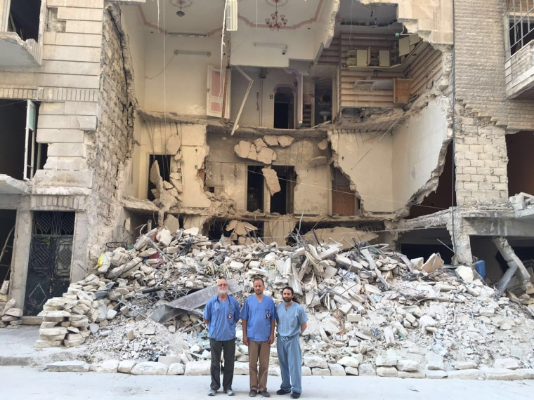 Dr. John Kahler, Dr. Zaher Sahloul and Dr. Samer Attar, American physicians from Chicago who volunteered with Syrian American Medical Society, stand in front of a bombed-out house in Eastern Aleppo in June 2016.