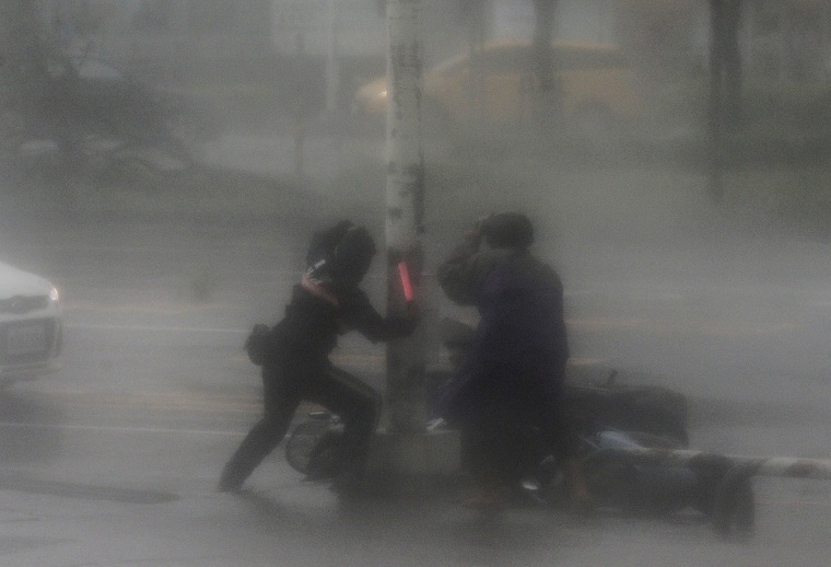 Image: A rescuer tries to assist a motorist victim as high winds and rain of Super Typhoon Meranti lash Kaohsiung