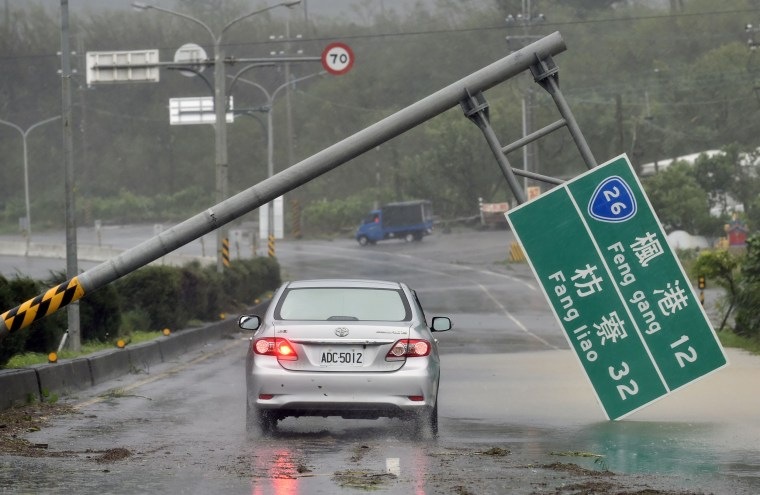 Image: A car drives past a collapsed traffic sign