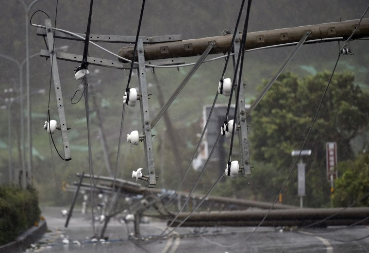 Image: Collapsed power lines partially block a road in Pingtung county