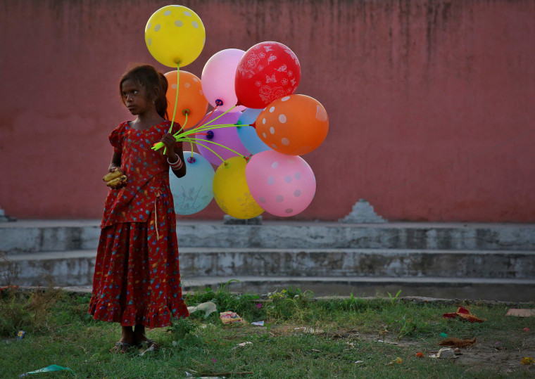 Image: A young girl sells balloons by the Yamuna River as devotees carrying idols of the Hindu god Ganesh, the deity of prosperity, immerse the idol on the last day of the ten-day-long Ganesh Chaturthi festival in Delhi