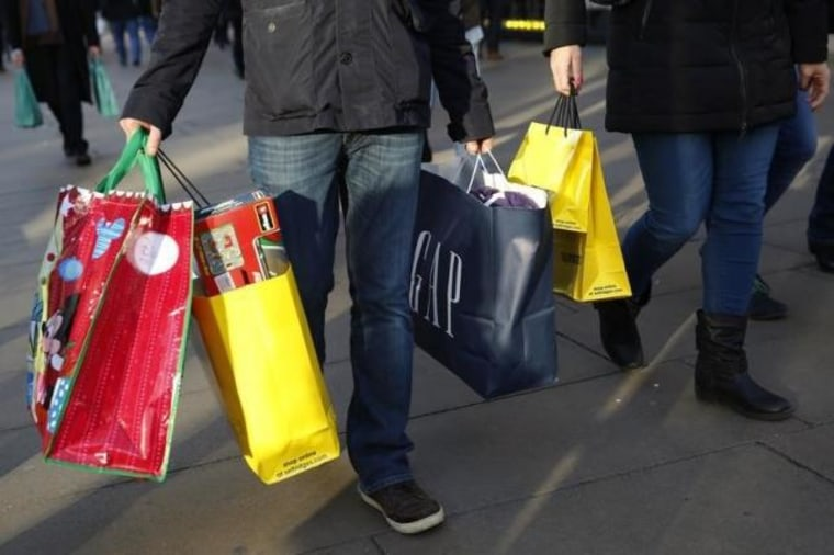 Shoppers carry bags along Oxford street during the final weekend of shopping before Christmas in London