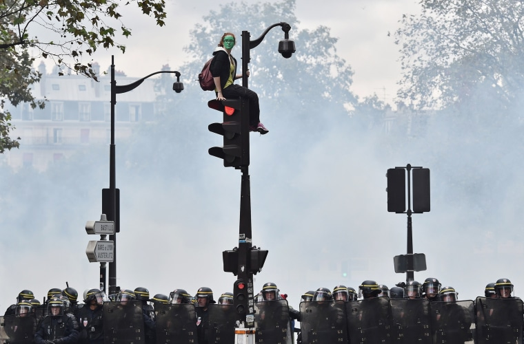 Image: A demonstrator in green face paint sits on a traffic light as French riot police secure the area during a protest against controversial labor reforms
