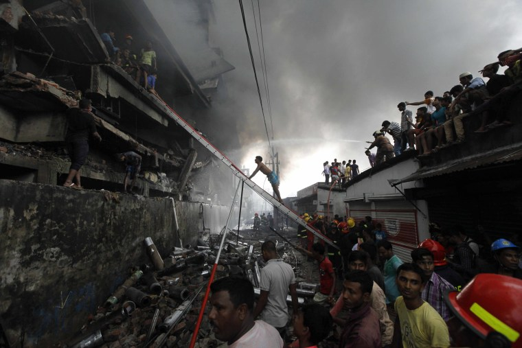 Image: Firefighters attempt to extinguish a fire at a garment packaging factory in the Tongi industrial area