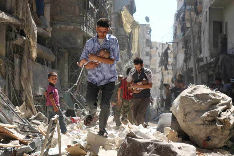 Image: Syrian men carrying babies make their way through the rubble of destroyed buildings