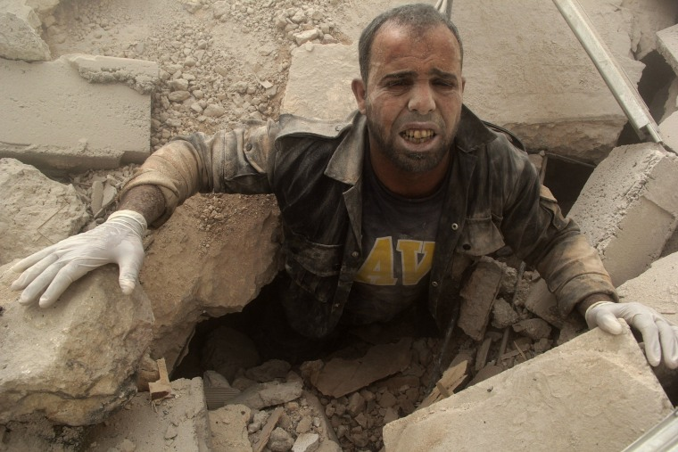 Image: A civil defence member is stuck under debris at a site hit by what activists said were two barrel bombs dropped by forces loyal to Syria's President Bashar al-Assad inAl-Shaar neighbourhood of Aleppo