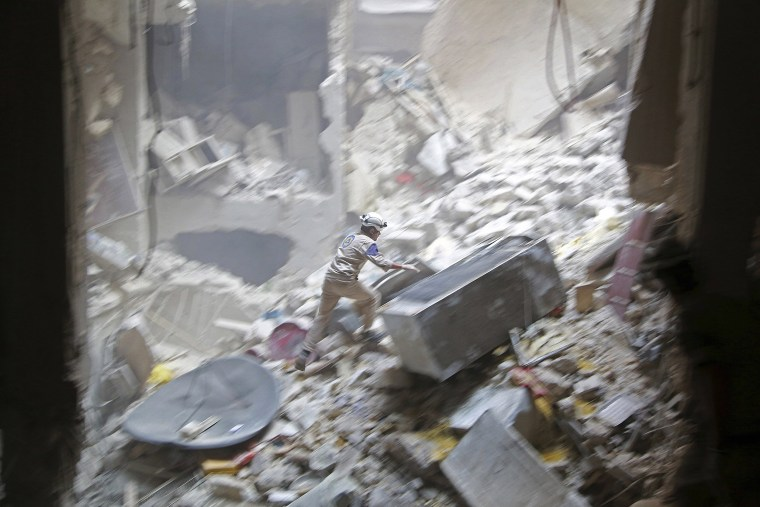 Image: A Civil defence member looks for survivors at a site hit by what activists said were two barrel bombs dropped by forces loyal to Syria's President Bashar al-Assad in the Al-Shaar neighbourhood of Aleppo J