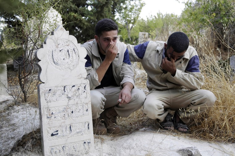 Image: Civil defense members mourn the death of their comrade, who died during what activists said were airstrikes carried out by the Russian air force, during his funeral in Ehsim town
