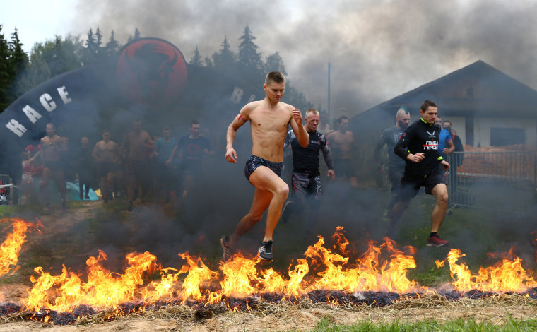 """Image: Participants take part in an extreme run \""""Bison race\"""" near the town of Logoisk"""