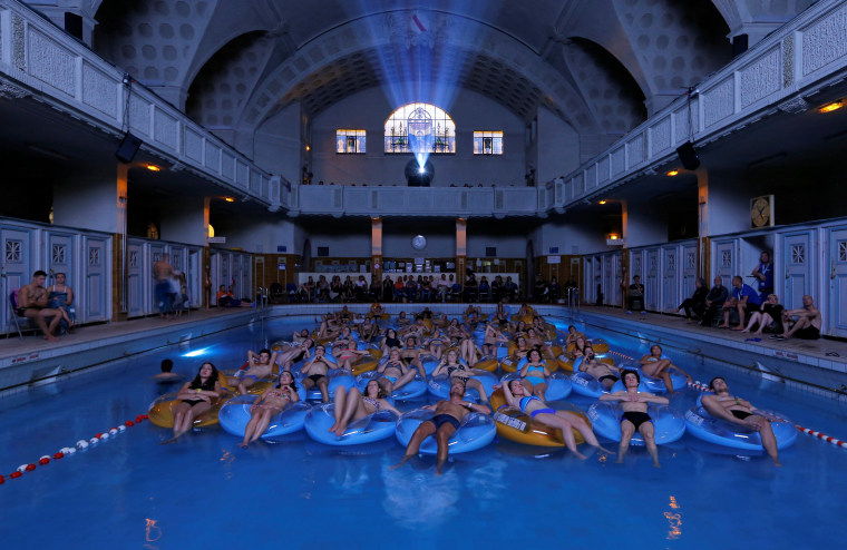 """Image: People attend the screening of the film \""""Jaws\"""" by director Steven Spielberg, screened at Strasbourg public baths during the European Fantastic Film Festival, in Strasbourg"""