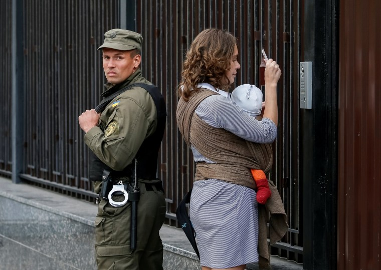 Image: A woman shows her passport to enter the Russian embassy and take part in the Russian parliamentary election as member of the National Guard stands guard in Kiev