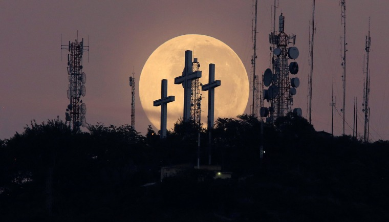 Image: The full moon is seen behind the hill of the three crosses in Cali