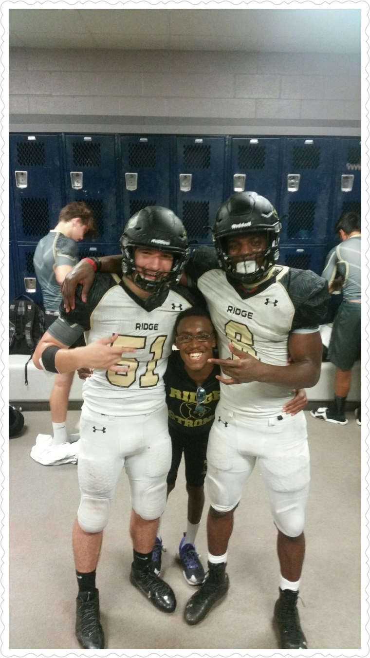 Norwood, the team manager, goofs off with a pair of Fossil Ridge football players.