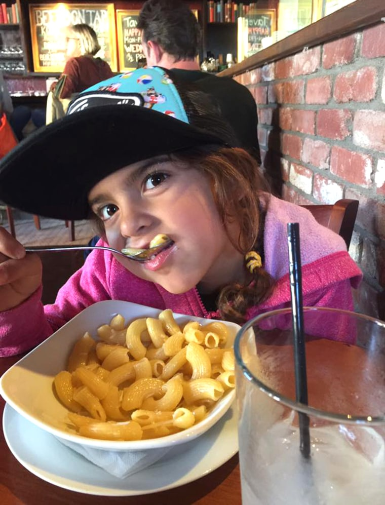 Ella Scott eating a big bowl of pasta while out to eat with her dad.