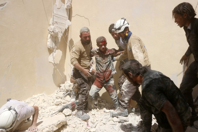 Image: A man rescued from rubble in Aleppo