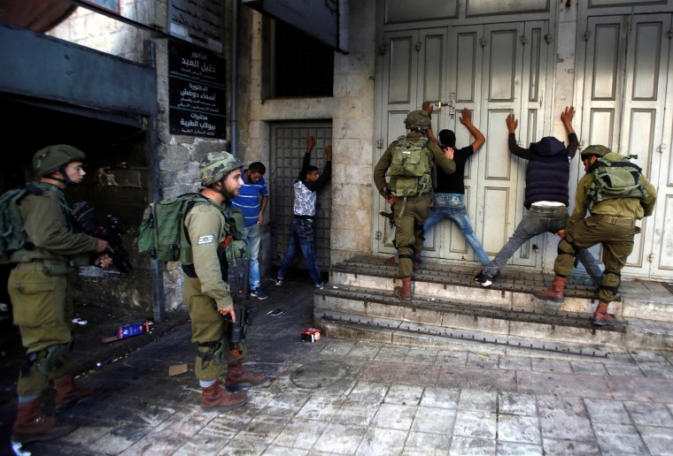 Image: Israeli soldiers search Palestinians during clashes in the West Bank city of Hebron