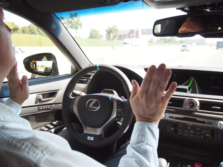 A driver briefly takes his hands off the steering wheel of Toyota Motor Corp.'s prototype car equipped with an automated highway driving support system while running on a highway in Detroit, Michigan, Sept. 5, 2014. The Japanese automaker demonstrated the car, which keeps drivers from straying out of lane on highways, to the media.