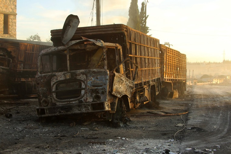 Image: Damaged aid trucks are pictured after an airstrike on the rebel held Urm al-Kubra town