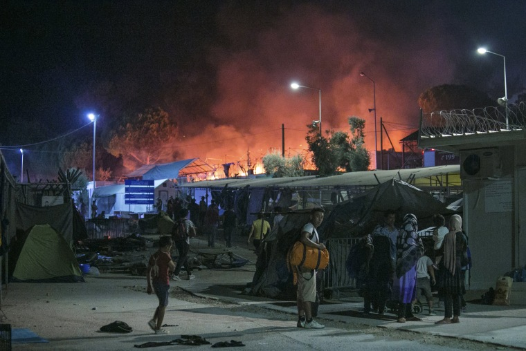 Image: Migrants hold their belonging as a large fire burns inside the Moria refugee camp