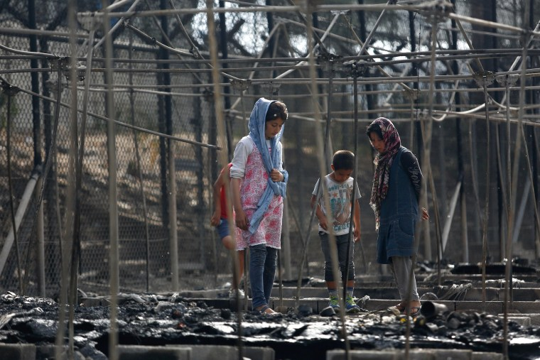 Image: Migrants stand among the remains of a burned tent at the Moria migrant camp, after a fire that ripped through tents and destroyed containers during violence among residents, on the island of Lesbos