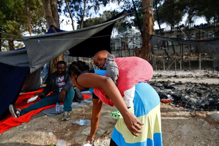 Image: A migrant woman carries a baby as she stands next to the remains of a burned tent at the Moria migrant camp