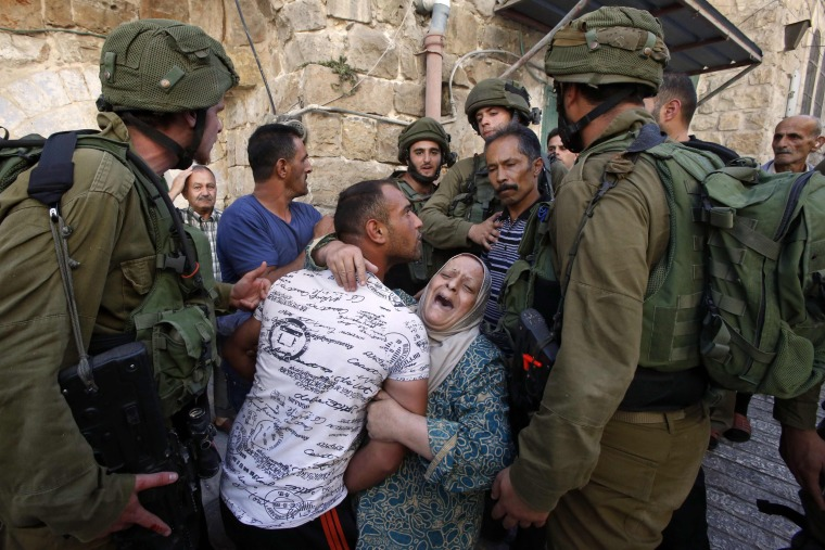 Image: A Palestinian woman tries to prevent the arrest of a Palestinian man by Israeli soldiers in the flashpoint city of Hebron