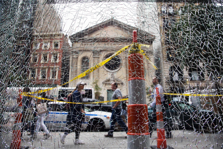 Image: New Yorkers pass a shattered storefront window on W. 23rd St. in Manhattan