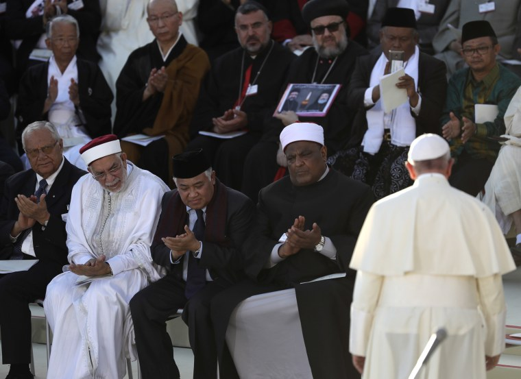 Image: Representatives of different religions applaud after Pope Francis delivered his speech during the closing event of an inter-religious prayer gathering