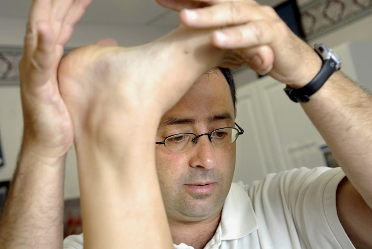 Dr. Larry Nassar works with a patient in East Lansing, Michigan, in 2008.
