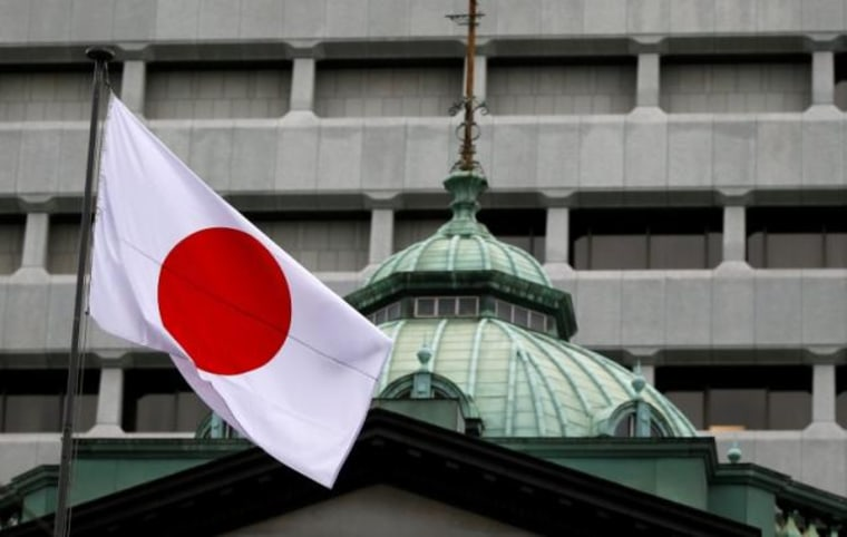 A Japanese flag flutters atop the Bank of Japan building in Tokyo