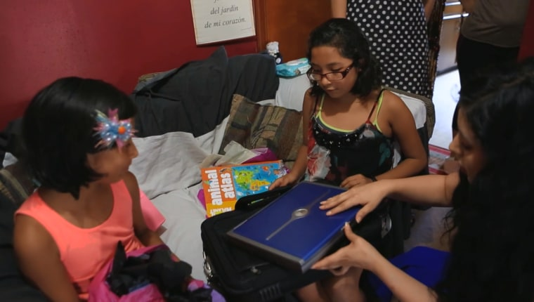 Stephanie Castillo, co-founder of Latina Girls Code, present a young Hispanic girl her first computer.