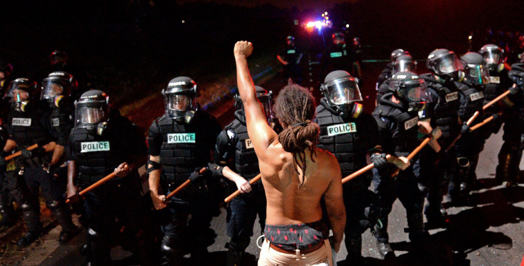 Image: A protester stands with his arm extended and fist clenched in front of a line of police officers in Charlotte