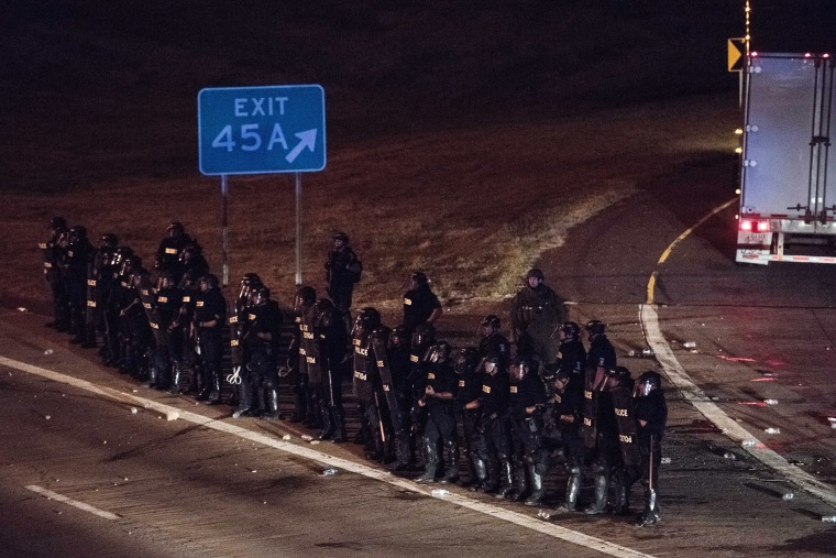 Image: Police officers take position at an onramp on I-85 during protests