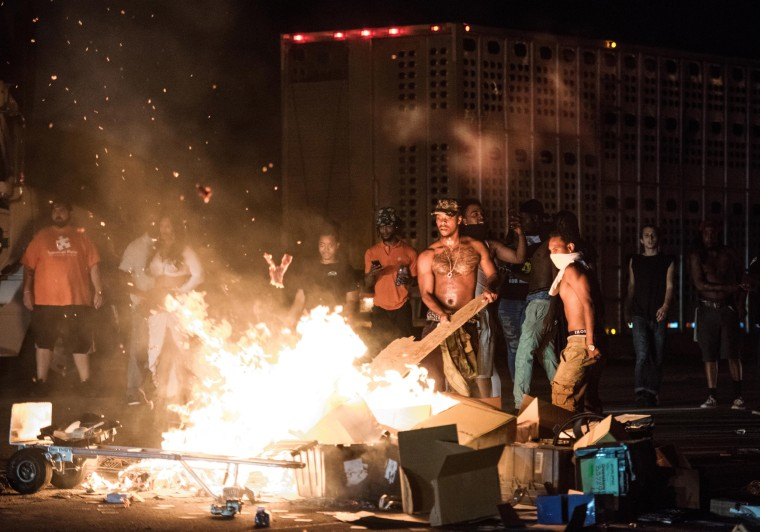 Image: People set cargo from tractor trailers on a fire on I-85 during protests