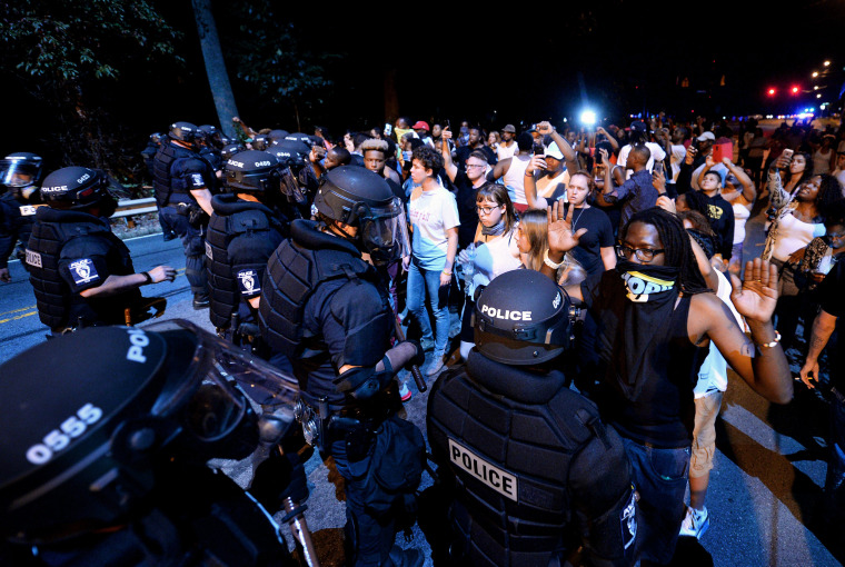Image: Police officers form a line in front of protesters in Charlotte
