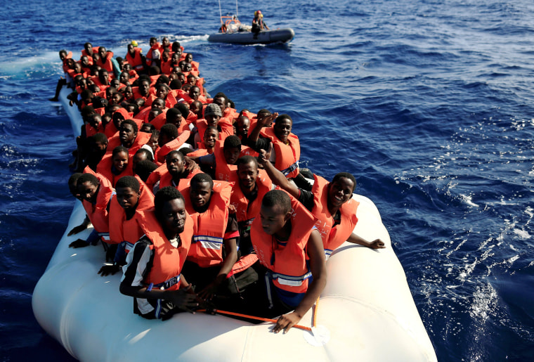 Image: An overcrowded dinghy with migrants from different African countries is followed by members of the German NGO Jugend Rettet as they approach the Iuventa vessel during a rescue operation in the Mediterranean Sea