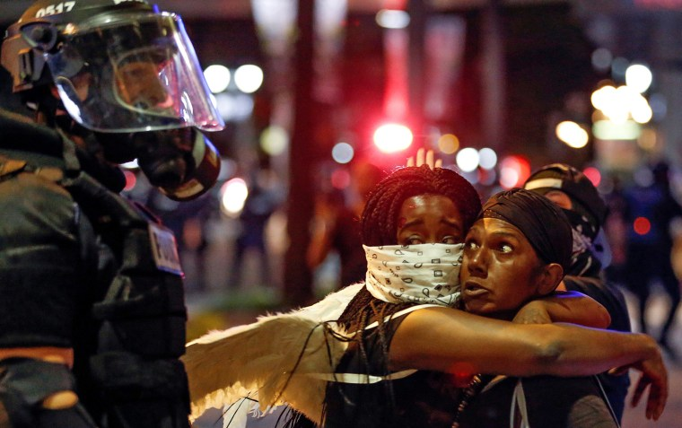 Image: Two women embrace while looking at a police officer in uptown Charlotte, NC during a protest of the police shooting of Keith Scott, in Charlotte