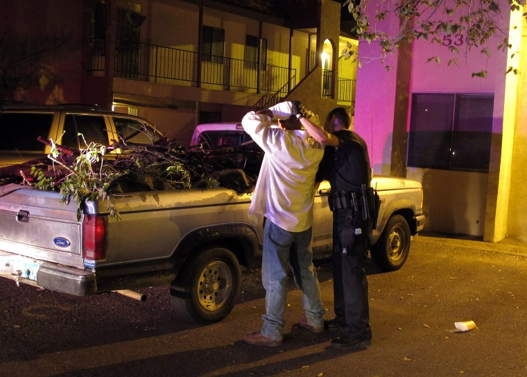 An Albuquerque officer frisks a man after he and two others were seen driving into an apartment known for drug activity in 2012.