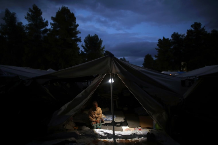 Image: A Syrian man sits inside his tents at Ritsona refugee camp north of Athens